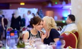 2 ladies at a table whispering secrets