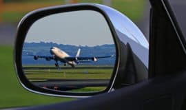 airplane taking off as viewed in the side mirror of a car