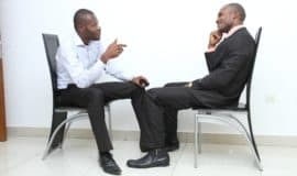 2 men sitting in chairs and talking