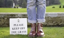 feet by a Keep Off the Grass sign