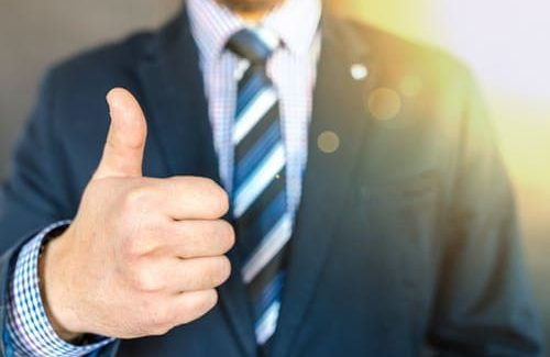 man in suit doing thumbs up